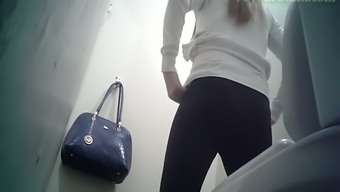 Attractive white colored blonde teenager in black panties filmed inside the toilet